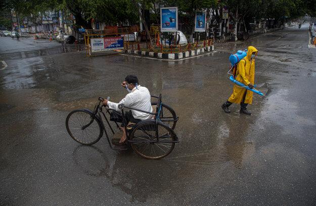 Muž na trojkolke a pracovník, ktorý dezinfikuje opustenú cestu v indickom Gauhate.
