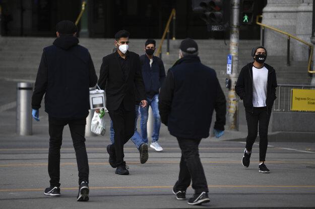 Obyvatelia austrálskeho mesta Melbourne s ochrannými rúškami proti šíreniu ochorenia COVID-19.