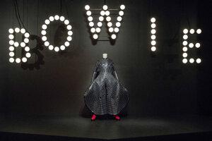 Lakovaný kožený odev a replika červených topánok z dielne japonského módneho návrhára Kansaia Jamamota je vystavený počas novinárskej prehliadky výstavy s názvom David Bowie.