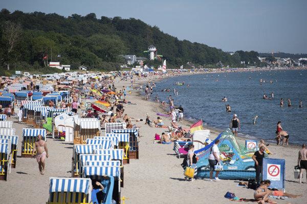 Ľudia oddychujú na pláži pri Baltickom mori v Nemecku.