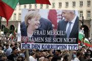 """Demonštranti držia transparent s nápisom """"Pani Merkelová! Nehanbíte sa za toho skorumpovanca?"""""""