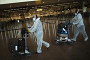 Cestujúci v ochranných odevoch, rúškach, štítoch a rukaviciach, ktorí cestujú na Srí lanku, tlačia na vozíku batožinu po bezpečnostnej kontrole na letisku v Bruseli v stredu 29. júla 2020.