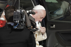 Pápež František si sníma rúško pri príchode na nádvorie San Damaso.