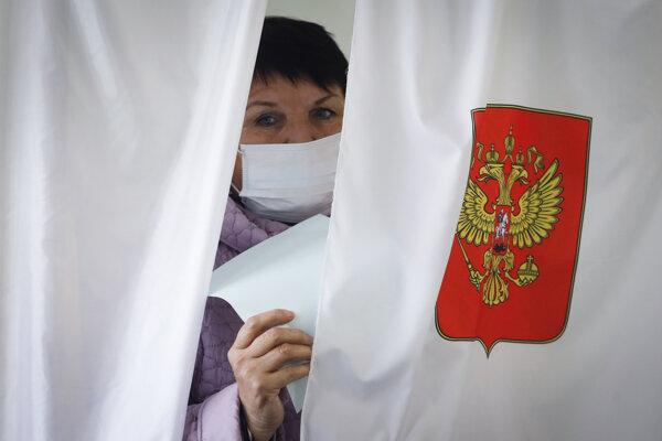 Žena s ochranným rúškom počas regionálnych volieb v ruskom Luppolove.