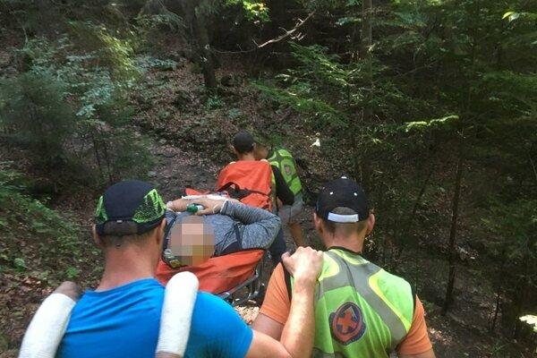 Záchranári znášali zraneného k autu na nosidlách.