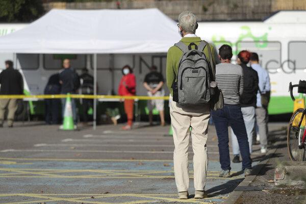 Ľudia stoja v rade pred mobilnou testovacou jednotkou na koronavírus na parkovisku v Portsmouthe.