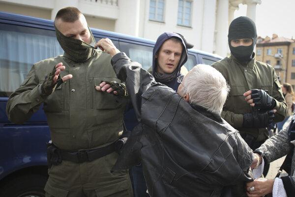 Protestujúca žena strháva členovi bezpečnostných zložiek masku.