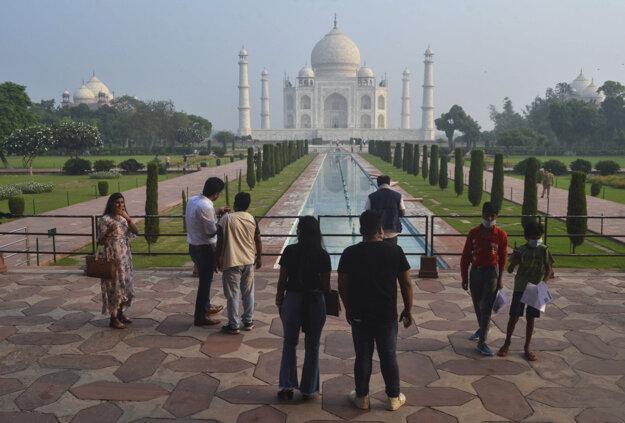 Koronavírus vo svete: Malá skupina indických turistov stojí pred pamätníkom Tádž Mahal v meste Ágra po jeho znovuotvorení.