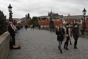 Ľudia kráčajú po Karlovom moste v Prahe. Česká republika zaznamenáva veľký nárast  prípadov ochorenia COVID-19 spôsobovaného novým druhom koronavírusu.