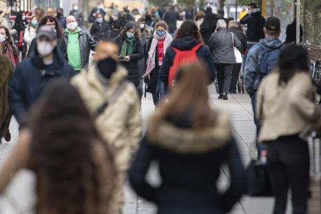 Ľudia s ochrannými rúškami kráčajú po ulici 14. októbra 2020 v Štuttgarte.