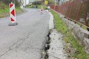 Trhliny v ceste  a naklonený plot. Aktuálny stav po dažďoch v Kluknave.