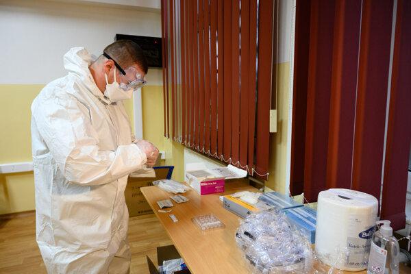 Zdravotník v odbernej miestnosti na Základnej škole Janka Matúšku v Dolnom Kubíne pripravuje testovaciu sadu počas pilotného testovania miestneho obyvateľstva v rámci operácie Spoločná zodpovednosť.