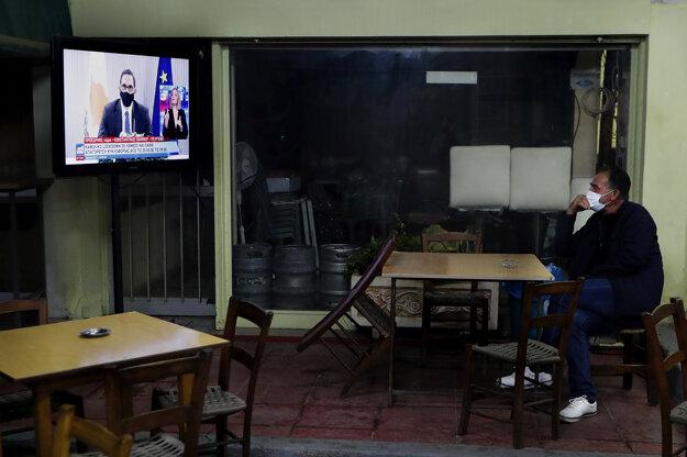 Cyperčan v jednom z podnikov v meste Nikózia sleduje tlačovú konferenciu ministra zdravotníctva Constantinosa Ioannoua, ktorý oznamuje potrebu prísnejších opatrení na zabránenie šírenia koronavírusu.