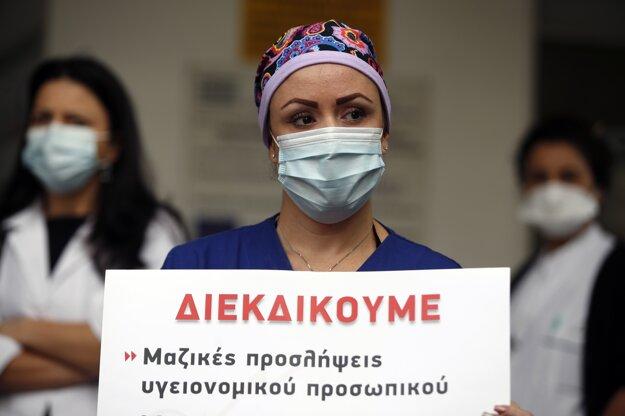 Zdravotná sestra na Jednotke intenzívnej starostlivosti s ochranným rúškom na zabránenie šíreniu nového koronavírusu drží transparent počas protestu pred nemocnicou Evangelismos v Aténach.