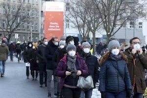 Ľudia s ochrannými rúškami čakajú v rade na prvé hromadné testovanie na nový druh koronavírusu vo Viedni.