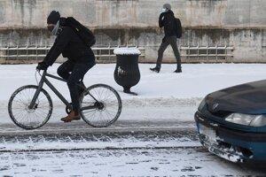 Cyklista jazdí po zasneženej Hlavnej ulici v Košiciach.