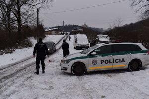 Pred osadou hliadkujú policajti.