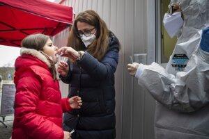 Dievča sa testuje počas PCR testov formou odberu kloktania v Bratislave.