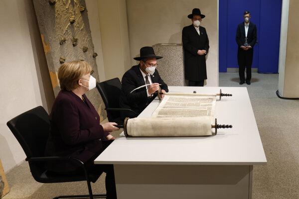 Nemecká kancelárka Angela Merkelová a rabín Shaul Nekrich pri ceremoniály dokončenia zvitku Tóry zo Sulzbachu, ktorý znovuobjavili v roku 2013.