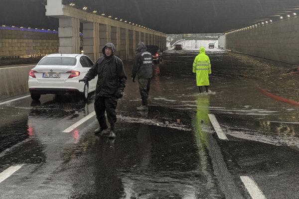 Policajti zastavujú dopravu pred zaplaveným podjazdom v tureckom meste Izmir.