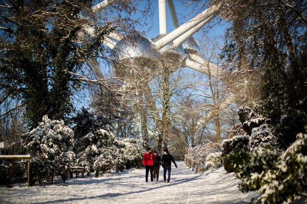 Ľudia kráčajú pri Atómiu počas prechádzky v zasneženom parku Laeken v Bruseli.