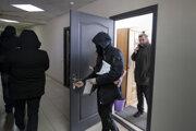 Policajti vynášajú dokumenty a počítače z kancelárie Bieloruskej asociácie novinárov.