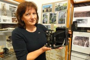 Kornélia Nemešová z múzea ukazuje jeden z najstarších vystavených fotoaparátov.