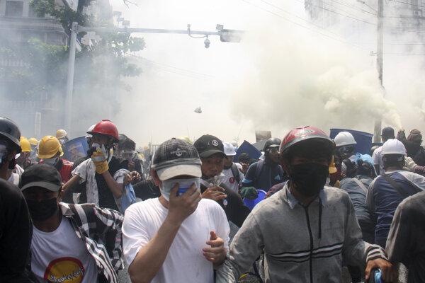 Demonštranti bežia pred slzotvorným plynom počas protestu proti vojenskej okupácii, v mjanmarskom meste Rangún.