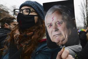 Protivládna demonštrantka s obrazov lídra poľskej vládnucej strany Jaroslawa Kaczynského.