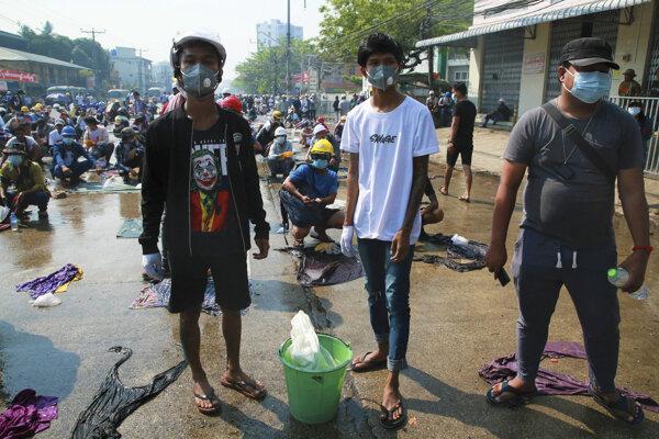 Protestanti s pripravenou vodou proti slzotvornému plynu