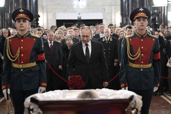 Putin stojaci pri rakve.