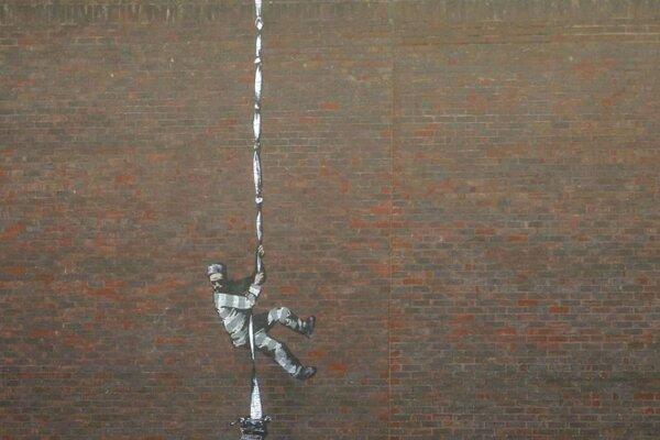 Dielo namaľované na múre väznice z červených tehál zobrazuje muža, ktorý sa snaží utiecť pomocou zviazaných plachiet.