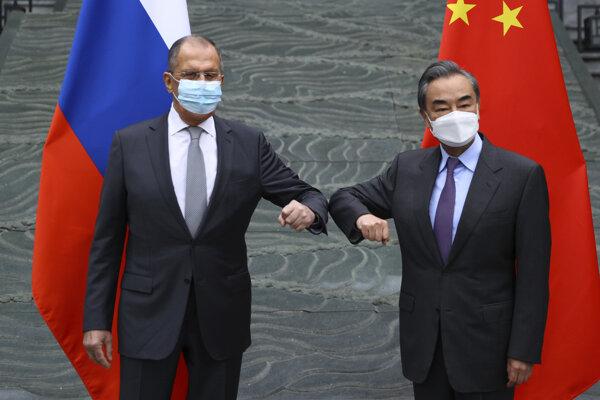 Ruský minister zahraničných vecí Sergej Lavrov (vľavo) a jeho čínsky rezortný kolega Wang I sa zdravia lakťami počas stretnutia v čínskom meste Kuej-Lin.
