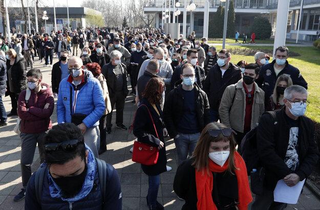 Rad cudzincov čakajúcich na očkovanie proti Covidu-19 pred očkovacím centrom v Belehrade.