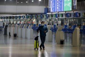 Cestujúci s ochranným rúškom kráča s kufrom v prázdnej hale medzinárodného letiska Eleftheriosa Venizelosa v Aténach.