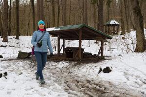 Turistka pri prameni minerálnej vody Štavica nad rekreačnou oblasťou Sigord.