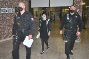 Policajti vedú mladšiu Bohuslavu na súd.