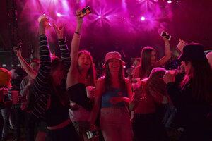 Účastníci prvého hudobného festivalu bez protipandemických obmedzení v liverpoolskom Sefton Parku.