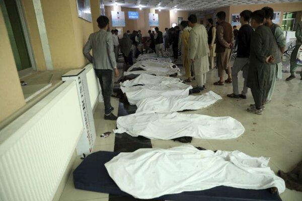 Afganskí muži identifikujú telá obetí po výbuchu bomby, ku ktorému došlo v blízkosti školy v afganskom hlavnom meste Kábul v sobotu 8. mája 2021.