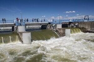 Ľudia sledujú vodu pri nápustnom objekte pri obci Vojka nad Dunajom. Na toku Dunaja sa uskutočňujú simulované a kontrolované záplavy.