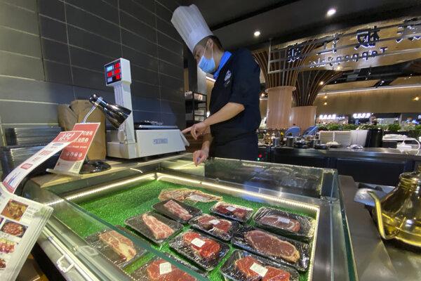 Predavač váži mäso v predajni v Pekingu.