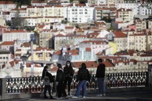Mladí ľudia v rúškach s výhľadom na historické centrum Lisabonu.