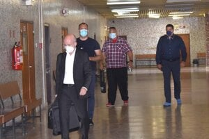 Obžalovaní a ich obhajca prichádzajú na súd.