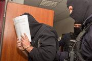 Bývalý šéf kontrarozviedky SIS Peter Gašparovič prichádza v sprievode polície na Špecializovaný trestný súd v Pezinku 6. decembra 2020.
