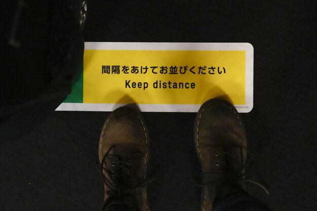Fotografka stojí na značke, ktorá upozorňuje na dodržiavanie 2-metrového odstupu  počas čakania na overovanie platnosti svojej akreditácie.