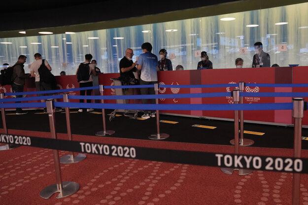 Ľudia čakajú na overovanie platnosti svojej akreditácie na letné olympijské hry na letisku v Tokiu.