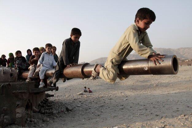Afganské deti sa hrajú na kanóne zničeného sovietskeho tanku.