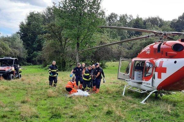 Prenášanie zranenej ženy na palubu vrtuľníka leteckej záchrannej služby.