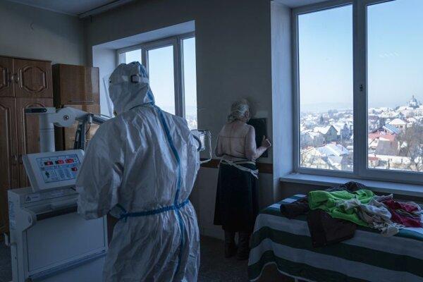 Zdravotný pracovník v špeciálnom ochrannom odeve (chrbtom) pripravuje poacientku s ochorením COVID-19 na röntgen pľúc v nemocnici v meste Kolomija na západe Ukrajiny.