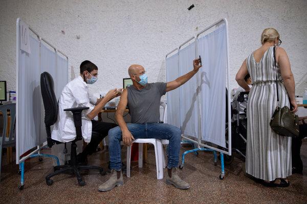 Izraelčan si robí fotografiu počas toho, ako dostáva tretiu vakcínu proti covidu-19 od Pfizer/BioNTech. V krajine už sprístupnili posilňovaciu dávku pre ľudí nad 12 rokov.